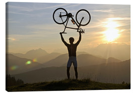 Canvas  Man holding a racing bike above his head - imageBROKER