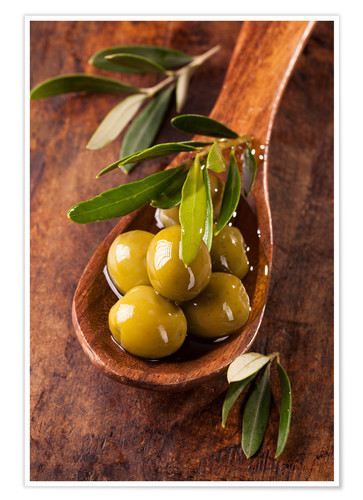 Premium poster Spoon with green olives on a wooden table